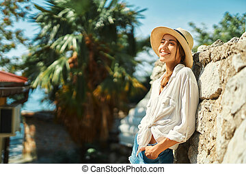 Happy female tourist in straw hat, white shirt standing by old stone wall on vacation in Thailand, smiling and enjoying solo travel, sightseeing city street. Tourism and travel concept.