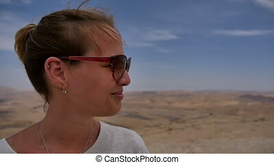 Happy female traveller enjoying desert view from cliff's edge