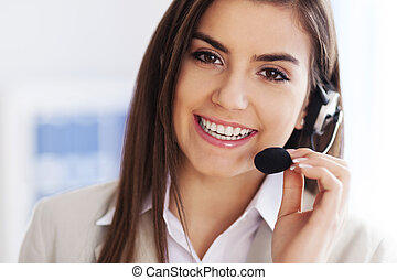 Happy female wearing headset and looking at camera