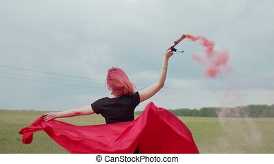 Happy female with smoke bomb whirling outdoors - Close-up of...