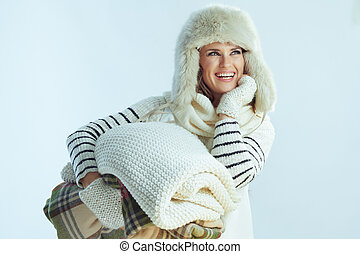 happy female with stack of warm blankets looking at copy space