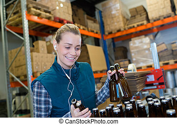 happy female worker on the production line of beer factory