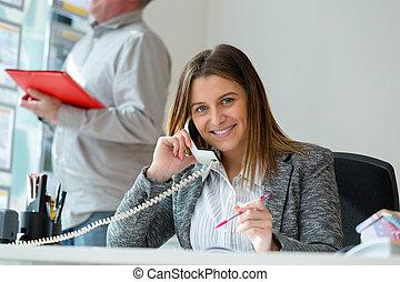 happy female worker talking phone in office