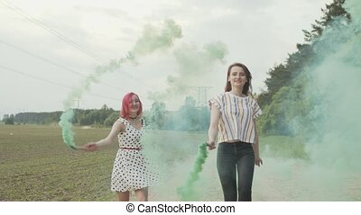 Carefree young women enjoying leisure and jumping in clouds of colorful smoke on country road. Laughing females with colored smoke bombs joyfully hopping and circling during walk in countryside.