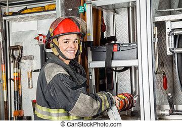 Happy Firefighter Fixing Water Hose In Truck - Portrait of...