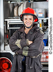 Happy Firefighter Standing Arms Crossed Against Firetruck