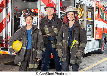 Happy Firefighters Standing Against Truck