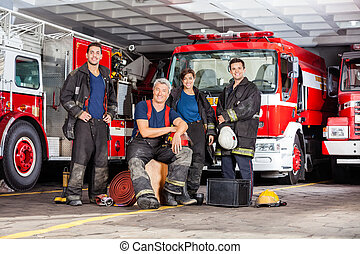 Happy Firefighter's Team With Equipment At Fire Station - ...