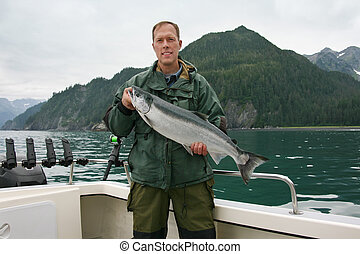 Happy fisherman in holds big silver salmon