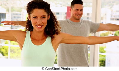 Happy fit couple smiling at the camera doing yoga at the gym