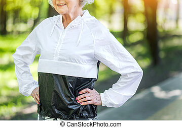 Happy fit senior woman exercising in city park