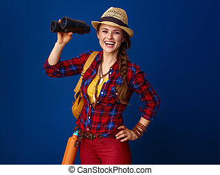 happy fit tourist woman isolated on blue with binoculars