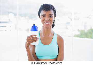Happy fit woman holding a bottle of water