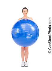 Happy fit woman holding exercise ball in front of her