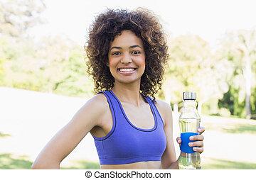 Happy fit woman holding water bottle