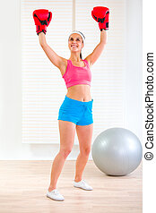 Happy fit woman in boxing gloves rejoicing success