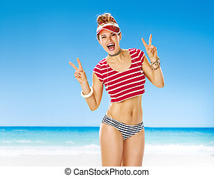 happy fit woman in red sun visor on seashore showing victory...