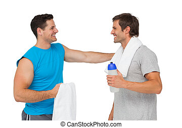 Happy fit young men with water bottle and towels