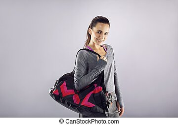 Happy fit young woman with gym bag