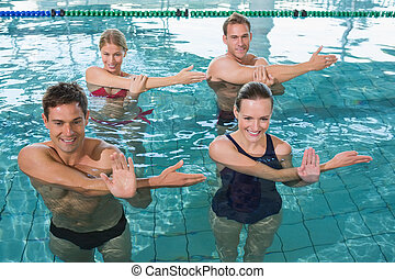 Happy fitness class doing aqua aerobics in swimming pool at...