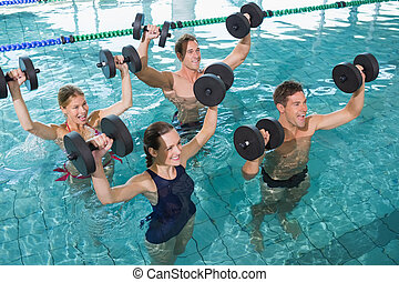 Happy fitness class doing aqua aerobics with foam dumbbells...