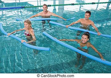 Happy fitness class doing aqua aerobics with foam rollers in...