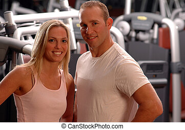 fitness couple - happy fitness couple in the gym