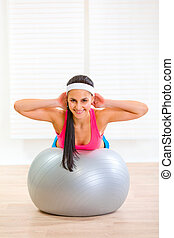 Happy fitness girl doing abdominal crunch on fitness ball