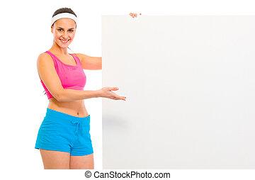 Happy fitness girl in sportswear holding blank billboard