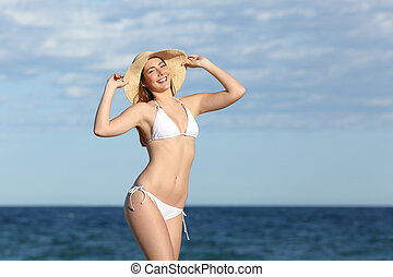 Happy fitness woman body posing on the beach with the...