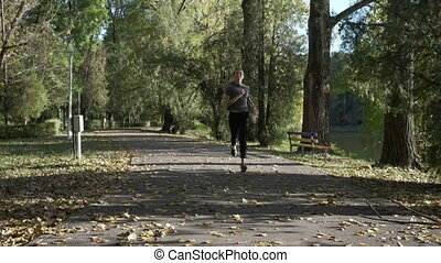 Happy fitness woman jogging and sweating in city park alone...