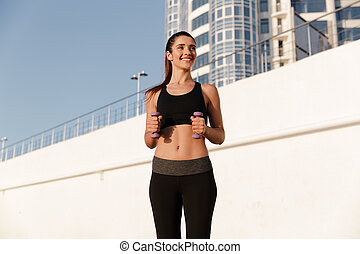 Happy fitness woman making exercises with dumbbells while training in morning