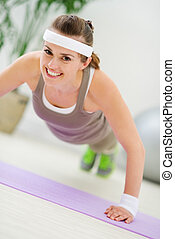 Happy fitness woman making push up exercise