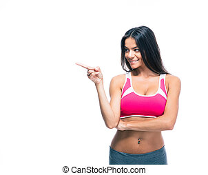 Happy fitness woman pointing finger away isolated on a white...