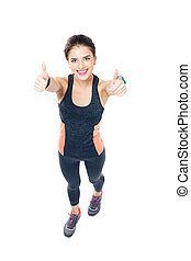 Happy fitness woman showing thumbs up