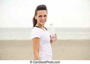 Happy Fitness Woman with Bottled Water at the Beach