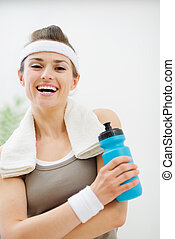 Happy fitness woman with towel on shoulders holding bottle of water