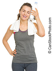 Happy fitness young woman enjoying bottle of water