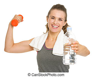 Happy fitness young woman holding dumbbells and giving bottle of water