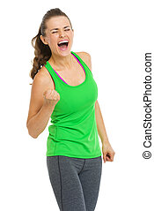 Happy fitness young woman making fist pump gesture