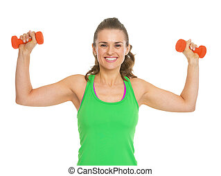 Happy fitness young woman making exercise with dumbbells