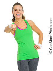 Happy fitness young woman pointing in camera