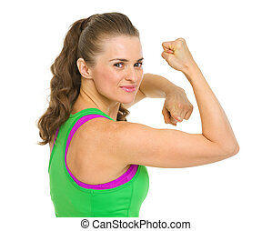 Happy fitness young woman pointing on biceps