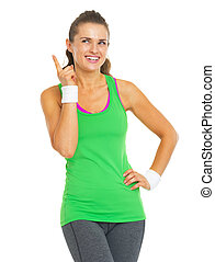 Happy fitness young woman pointing on copy space