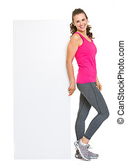 Happy fitness young woman showing blank billboard