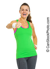 Happy fitness young woman showing thumbs up