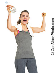 Happy fitness young woman with bottle of water rejoicing...