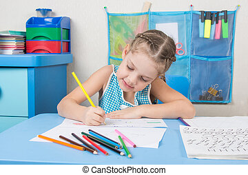 Happy five year old girl chose enthusiastically draws with colored pencils
