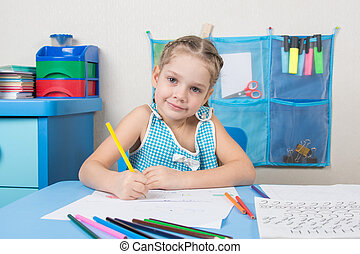 Happy five year old girl draws pencil and looked into the frame