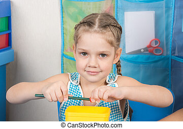 Happy five year old girl sharpens a pencil sharpener small